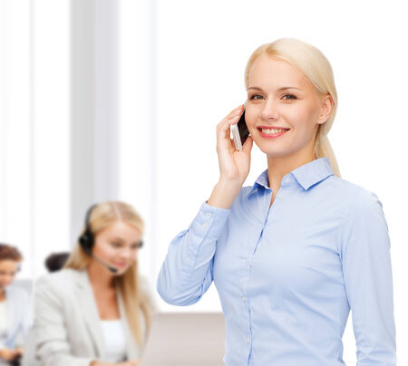 business, technology, education and people concept - smiling young businesswoman with smartphone making call in office photo