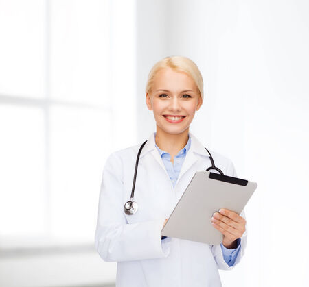 new medicine: healthcare, technology and medicine concept - smiling female doctor with stethoscope and tablet pc computer Stock Photo