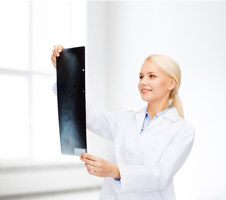 roentgenogram: healthcare, medicine and radiology concept - smiling female doctor looking at x-ray over white room background Stock Photo