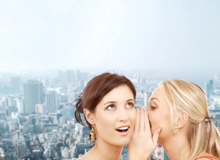 friendship, happiness and people concept - two smiling women whispering gossip