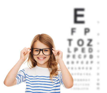examen de la vista: la educación, la escuela y el concepto de visión - una sonrisa de niña linda con anteojos negros Foto de archivo