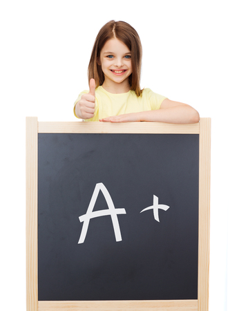 people, childhood, school, gesture and education concept - smiling little girl with blackboard showing thumbs up photo