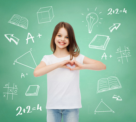advertising, gesture, charity, education and people - smiling little girl in white blank t-shirt showing heart-shape gesture over green board with doodles background Stock Photo