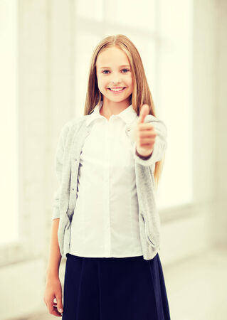 education and school concept - little student girl showing thumbs up at school photo