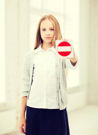education, school and anti-bullying concept - student girl showing stop sign photo