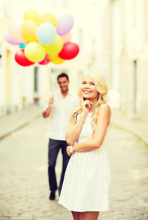 summer holidays, celebration and relationships concept - woman and man with colorful balloons in the city photo
