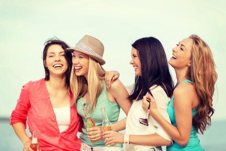 nonalcoholic beer: summer holidays and vacation concept - smiling girls with drinks on the beach