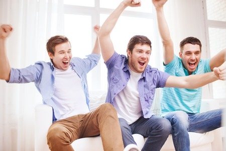 friendship, sports and entertainment concept - happy male friends supporting football team at home