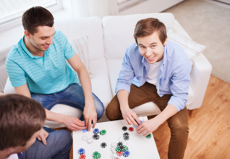 room mate: leisure, games, friendship, gambling and entertainment - three smiling male friends playing cards at home