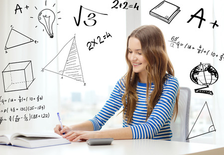 making notes: education, technology and home concept - smiling student girl with book, notebook and calculator