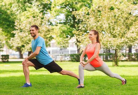 フィットネス、スポーツ、トレーニングやライフ スタイル コンセプト - 屋外ストレッチ カップルの笑顔