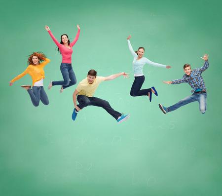 幸福、自由、友情、教育、人々 の概念 - 緑色の基板の背景の上の空気中のジャンプ笑顔ティーンエイ ジャーのグループ