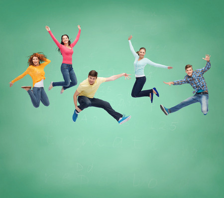 lady fly: happiness, freedom, friendship, education and people concept - group of smiling teenagers jumping in air over green board background