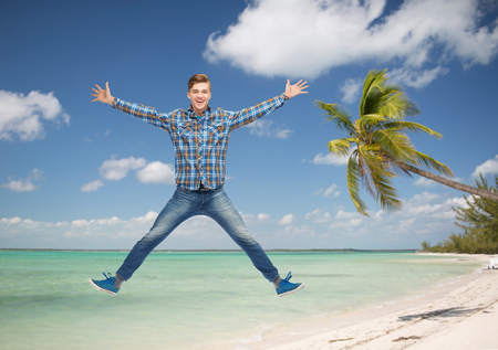 flying man: summer vacation, travel, tourism, freedom and people concept - smiling young man jumping in air over tropical beach background Stock Photo