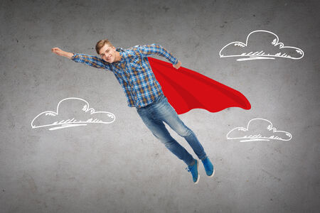 flying man: happiness, freedom, movement and people concept - smiling young man flying in air over blue background concrete wall with drawing of clouds background Stock Photo