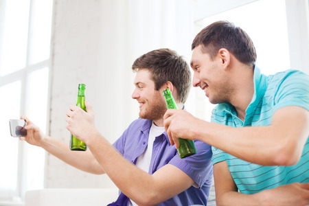 nonalcoholic beer: friendship, technology, drinks and home concept - smiling male friends with smartphone and beer at home