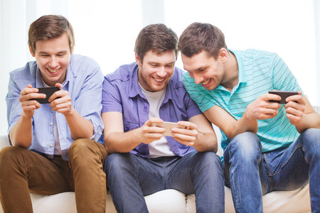 mobile telephones: friendship, technology and home concept - smiling male friends with smartphones at home