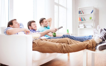 nonalcoholic beer: friendship, home, sports and entertainment concept - happy male friends with beer watching tv at home
