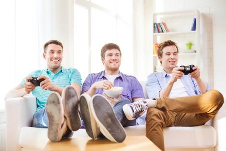 jugando videojuegos: la amistad, la tecnología, los juegos y el concepto de casa - sonrientes amigos masculinos que juegan juegos de video en casa
