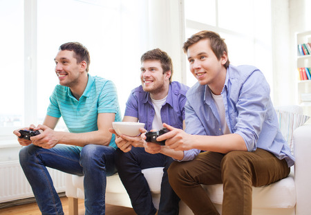 friendship, technology, games and home concept - smiling male friends playing video games at home photo
