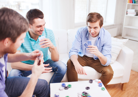 leisure, games, friendship, gambling and entertainment - three smiling male friends playing cards at home photo
