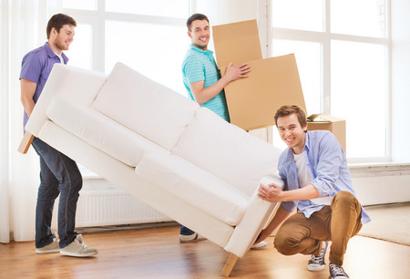 moving in: repair, furniture, decorating and home concept - smiling friends with sofa and cardboard boxes Stock Photo