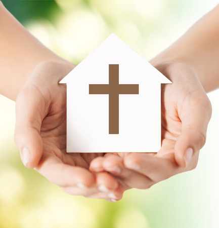 house of prayer: religion, christianity and charity concept - close up of woman hands holding paper house with christian cross symbol over green background
