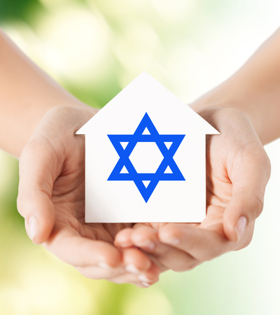 religion, judaism and charity concept - close up of woman hands holding house with star of david over green background photo