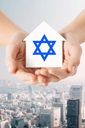jewish community: religion, judaism and charity concept - close up of woman hands holding house with star of david over city background