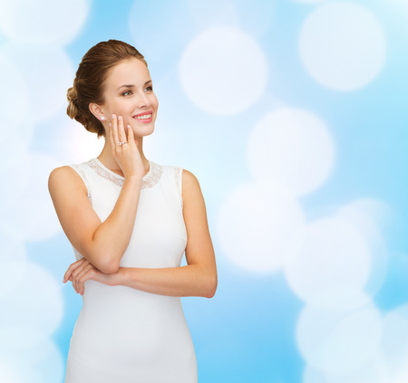 holidays, celebration, wedding and people concept - smiling woman in white dress wearing diamond ring over blue lights background Reklamní fotografie
