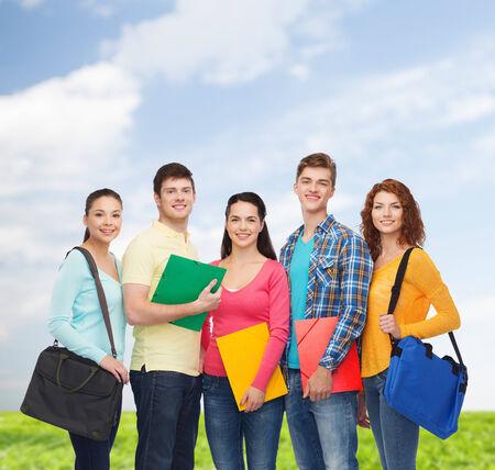 adolescentes estudiando: amistad, las vacaciones de verano, educación y concepto de la gente - grupo de adolescentes sonrientes con las carpetas y mochilas escolares sobre el cielo azul y la hierba de fondo