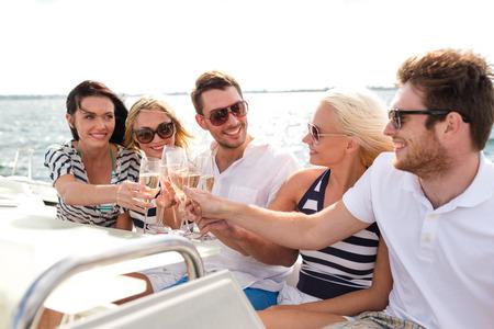 bateau voile: vacances, Voyage, mer, l'amitié et le peuple notion - souriant amis avec des verres de champagne sur yacht