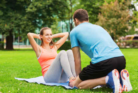 weight training: fitness, sport, training, teamwork and lifestyle concept - smiling woman with personal trainer doing exercises on mat outdoors