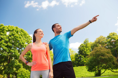 fitness, sport, training, technology and lifestyle concept - two smiling people outdoors photo