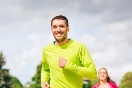 uomo felice: fitness, sport, amicizia e concetto di lifestyle - sorridente coppia in esecuzione all'aperto
