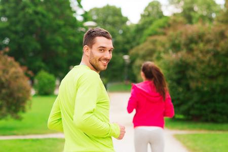 concept van fitness, sport, vriendschap en lifestyle - lachend paar lopen buitenshuis Stockfoto