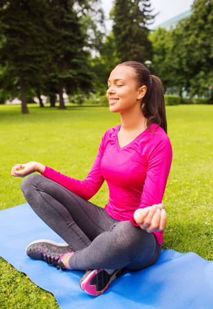 sport, meditation, park and lifestyle concept - smiling african american woman meditating on mat outdoors photo