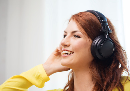 technology, music and happiness concept - smiling teenage girl in headphones at home photo