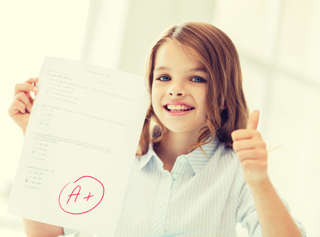 education and school concept - little student girl with test and A grade at school showing thumbs up photo