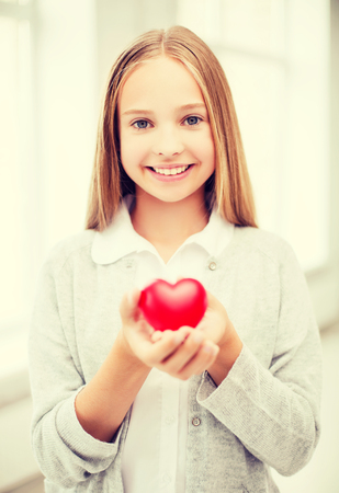 pre teen girls: health, charity and beauty concept - beautiful teenage girl showing red heart Stock Photo