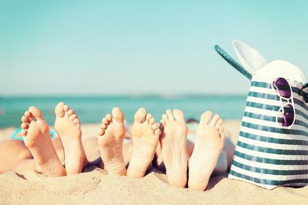 pies: vacaciones de verano, tomar el sol y pedicura concepto - tres mujeres tumbado en la playa con sombrero de paja, gafas de sol y el bolso