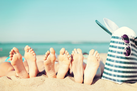 summer vacation, sunbathing and pedicure concept - three women lying on the beach with straw hat, sunglasses and bag Foto de archivo