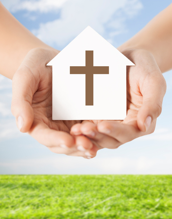 blue church: religion, christianity and charity concept - close up of woman hands holding paper house with christian cross symbol over blue sky with grass background