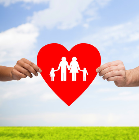 family support: health, love, adoption and relationships concept - closeup of multiracial couple hands with big red heart with family and kids over blue sky with grass background