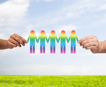 community, unity and teamwork concept - close up of multiracial couple hands holding paper chain gay people cutout over blue sky with grass background photo