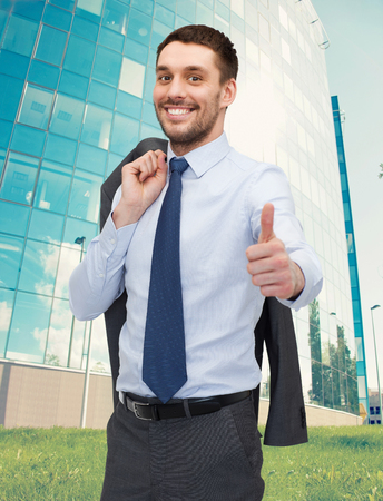 business, gesture and people concept - smiling young and handsome businessman showing thumbs up over business centre background photo