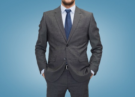 gray suit: business, people and office concept - close up of businessman over blue background