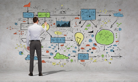 business, education and office people concept - businessman or teacher with marker writing or drawing scheme from back over concrete wall background Фото со стока
