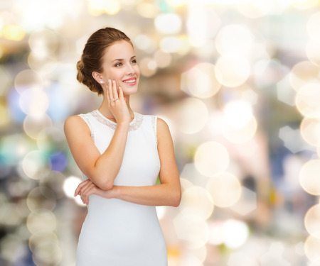 holidays, celebration, wedding and people concept - smiling woman in white dress wearing diamond ring over golden lights background photo