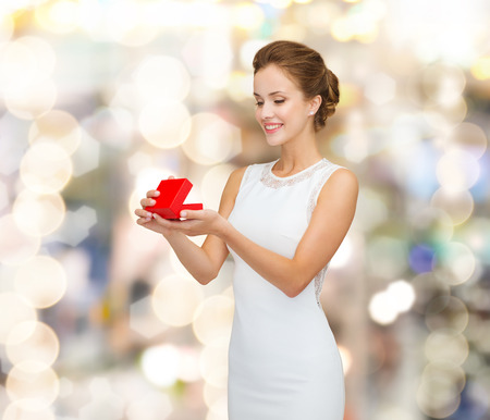 holidays, presents, wedding and happiness concept - smiling woman in white dress holding red gift box over shiny lights background